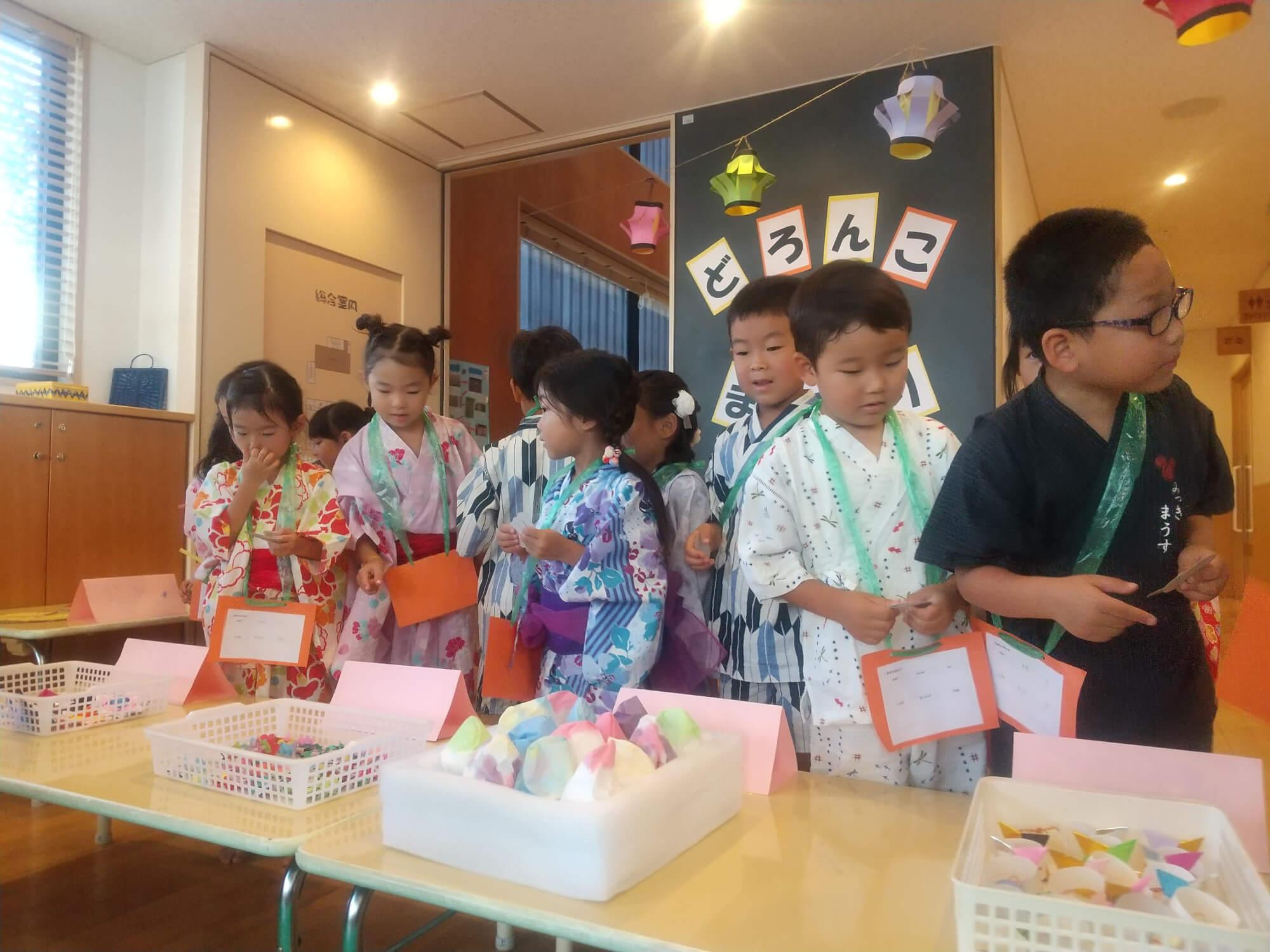 手作りのコインと商品でお買い物を楽しむ子どもたち