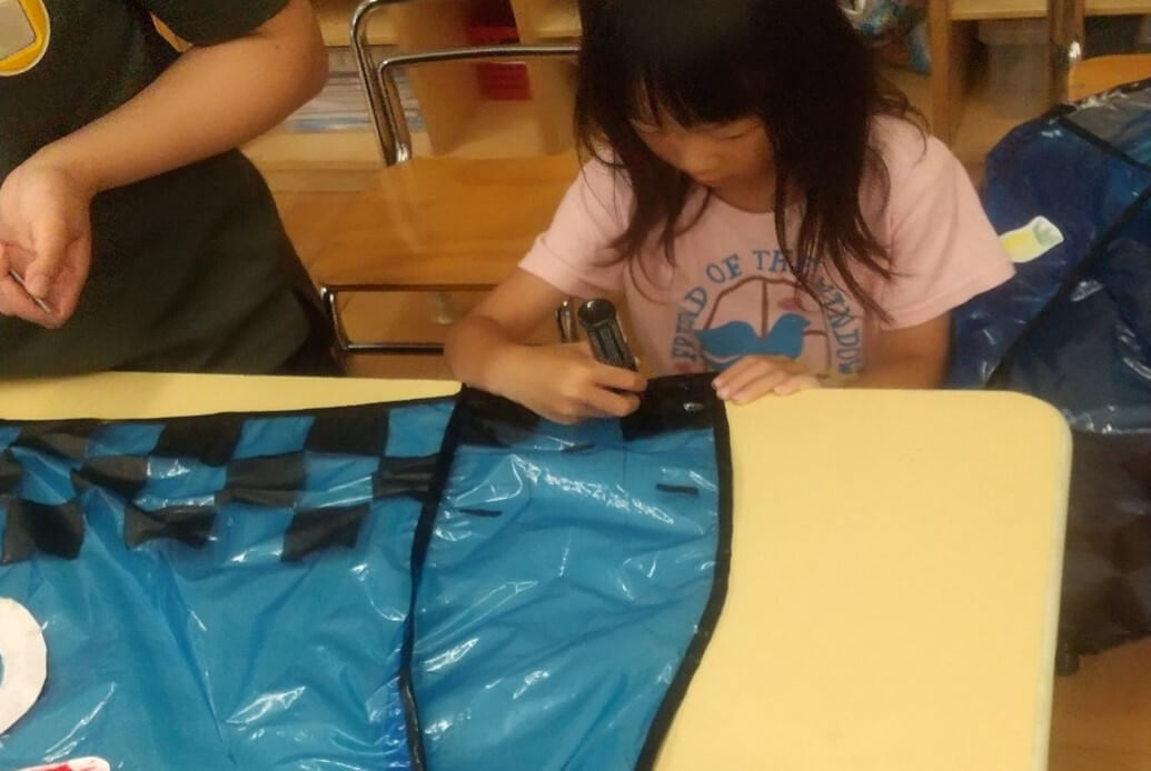 お祭用の装飾を作る子ども