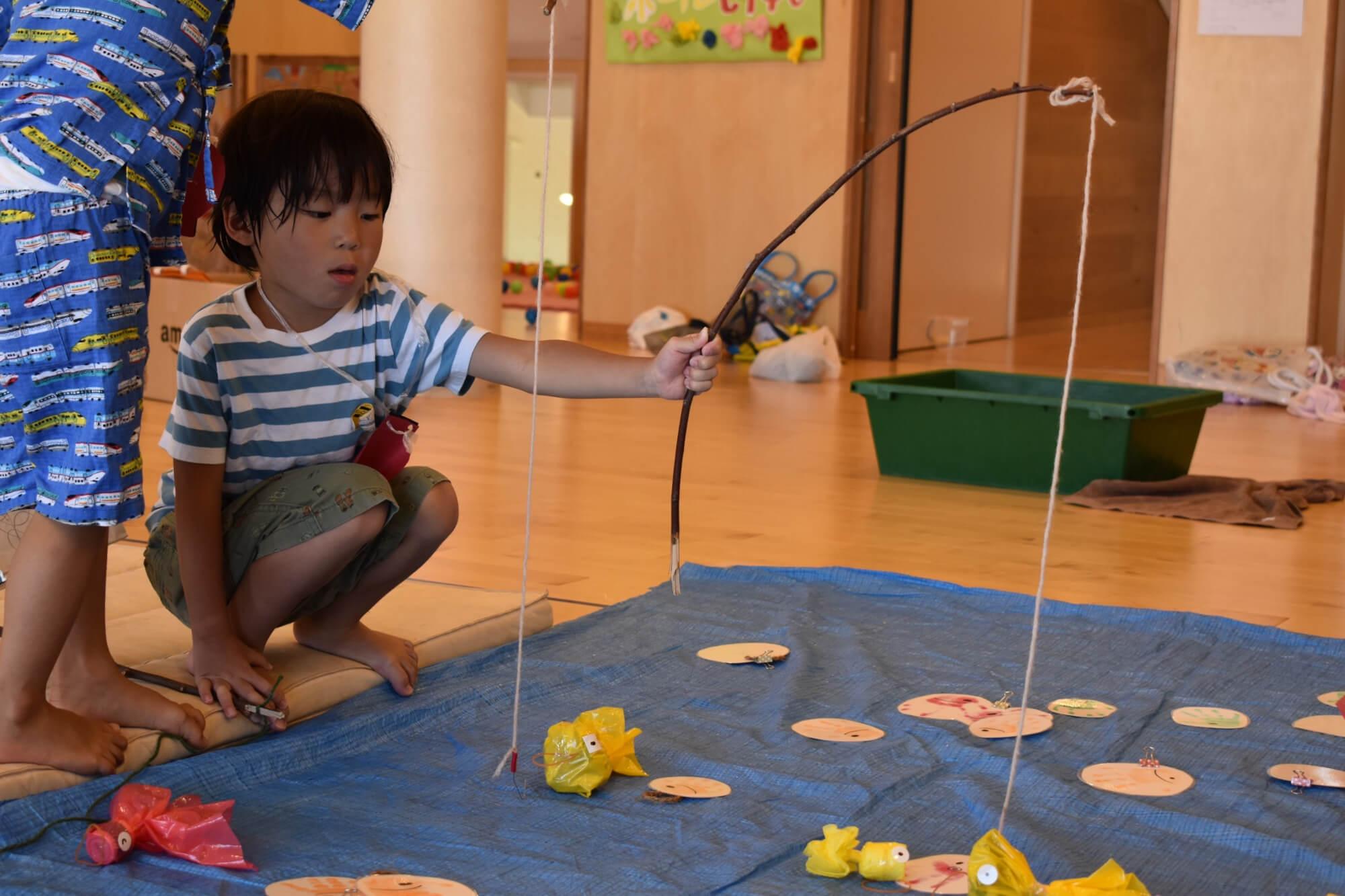 金魚すくいで遊ぶ子ども