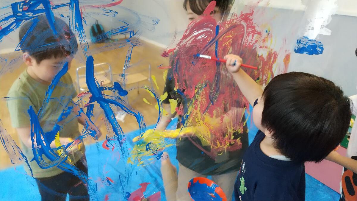 ビニールシートに絵の具を塗る子どもたち