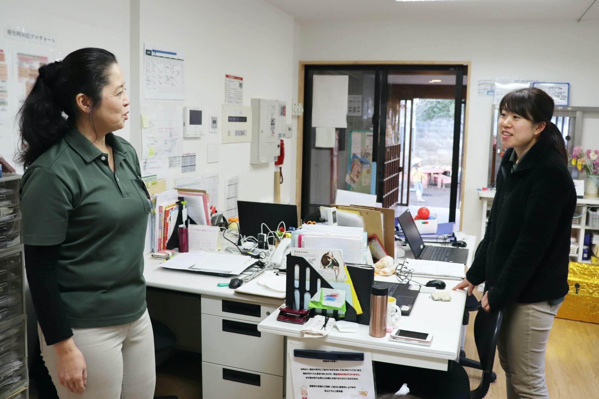 職員室にて職員と気軽にコミュニケーションをとる高井園長
