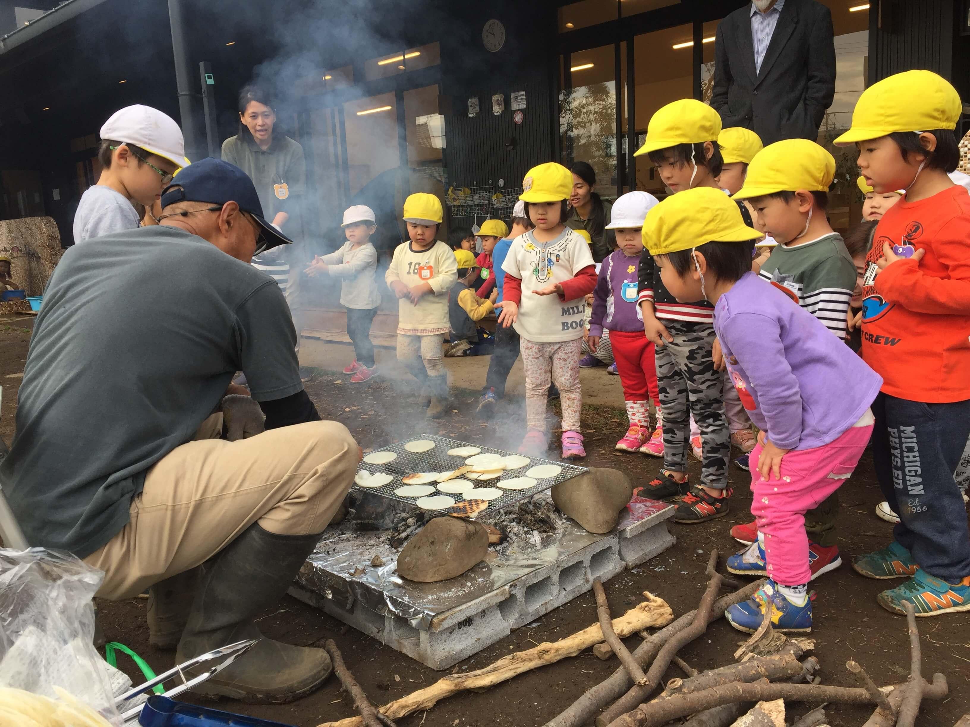 焚き火に集まる園児たち