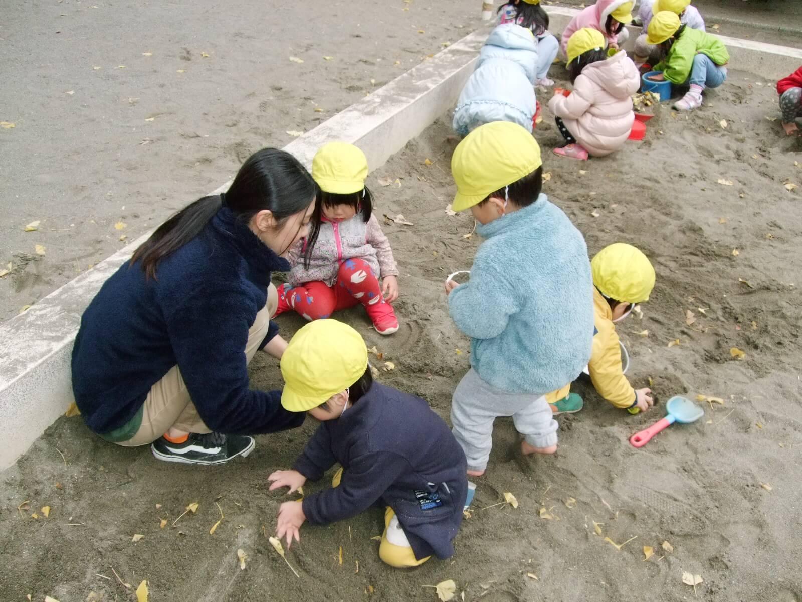 園児と砂遊びをする橋本さん
