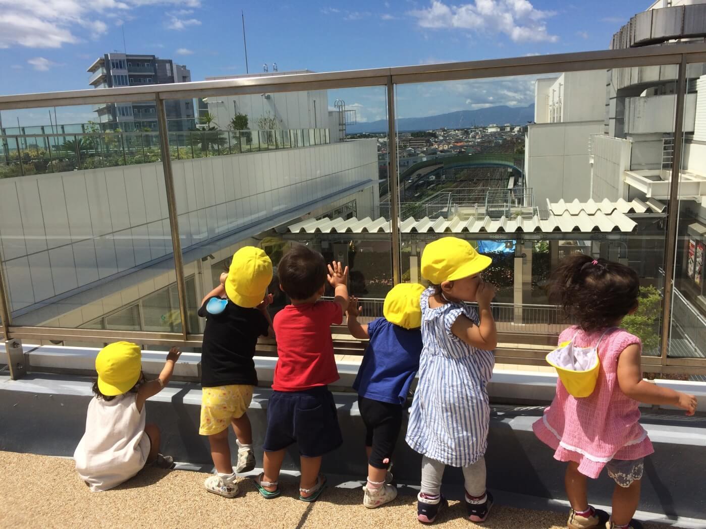 屋上から電車に手を振る子どもたち